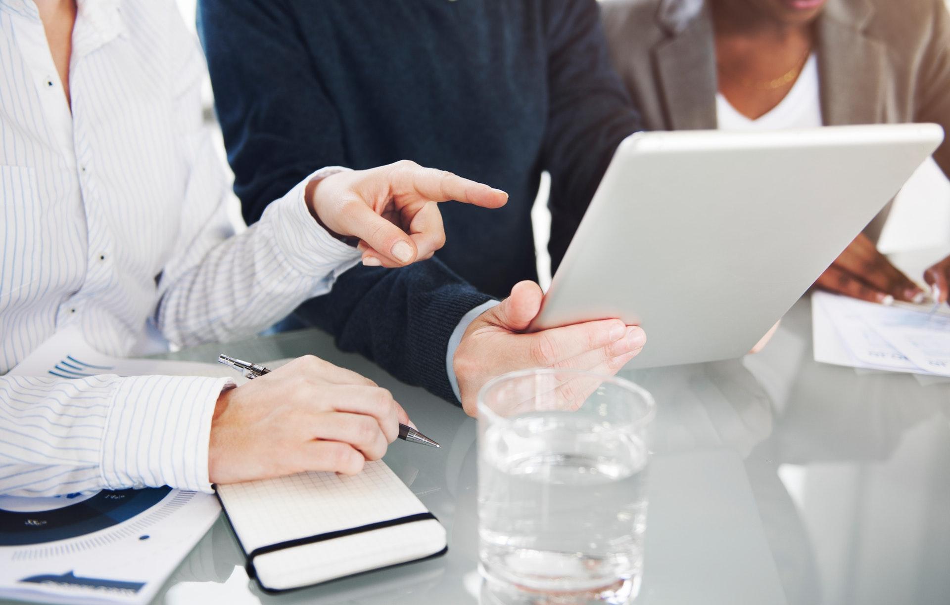 En entreprise, une femme montre un document du doigt